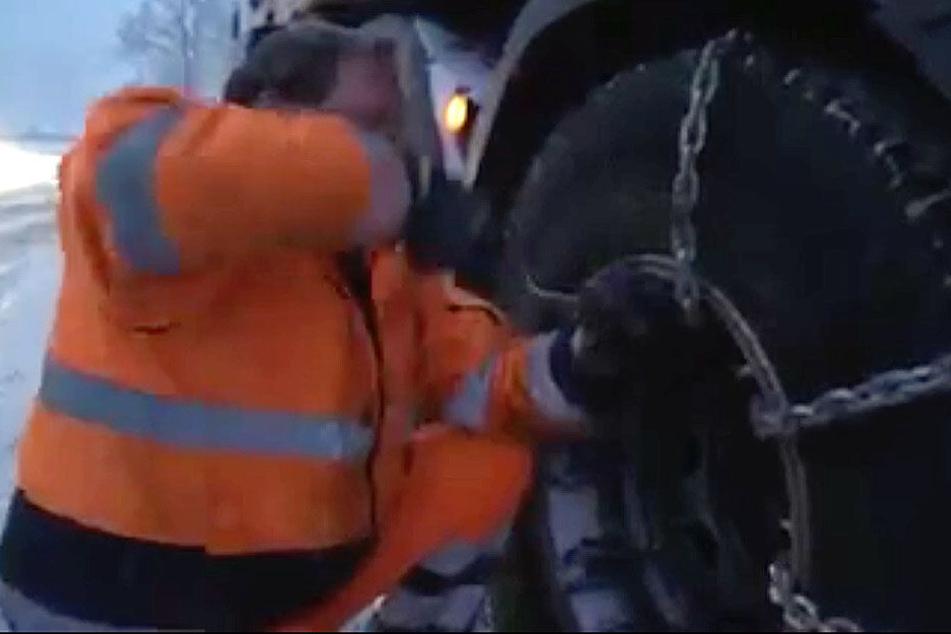 Der Lkw-Fahrer zieht Schneeketten auf.