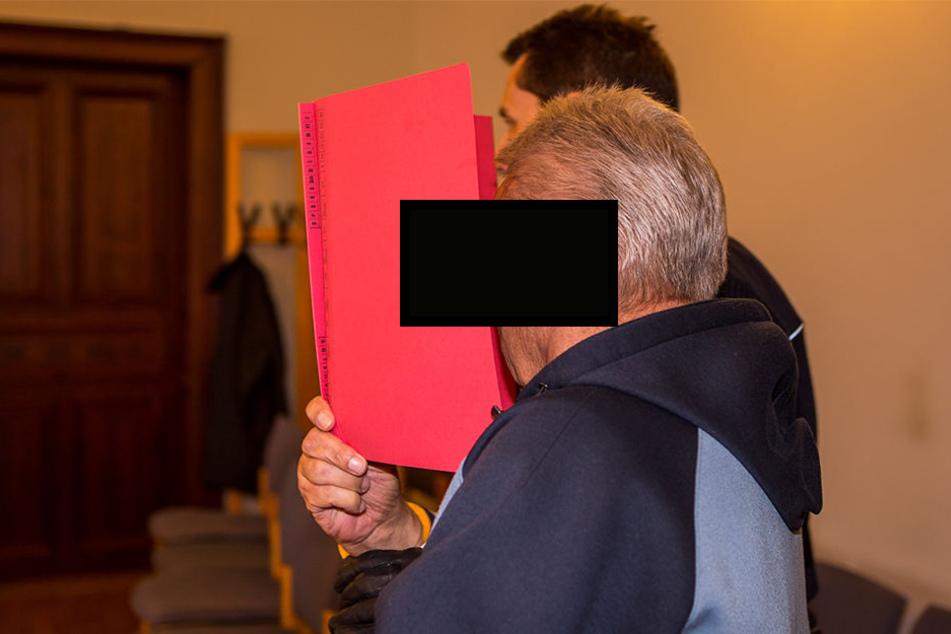 Versteckte sein Gesicht hinter einem roten Hefter: Kinderschänder Norbert H. (69) auf dem Weg zur Anklagebank.