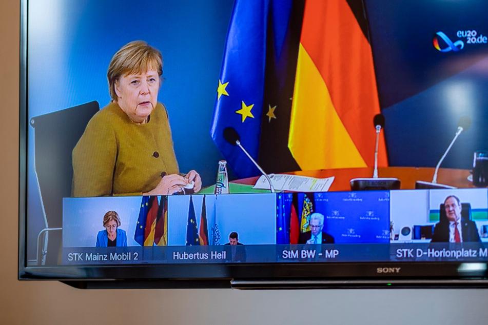 Angela Merkel (CDU), Bundeskanzlerin, spricht bei Beratungen der deutschen Ministerpräsidenten in einer Videokonferenz und ist dabei auf einem Monitor in der Staatskanzlei in Kiel zu sehen.