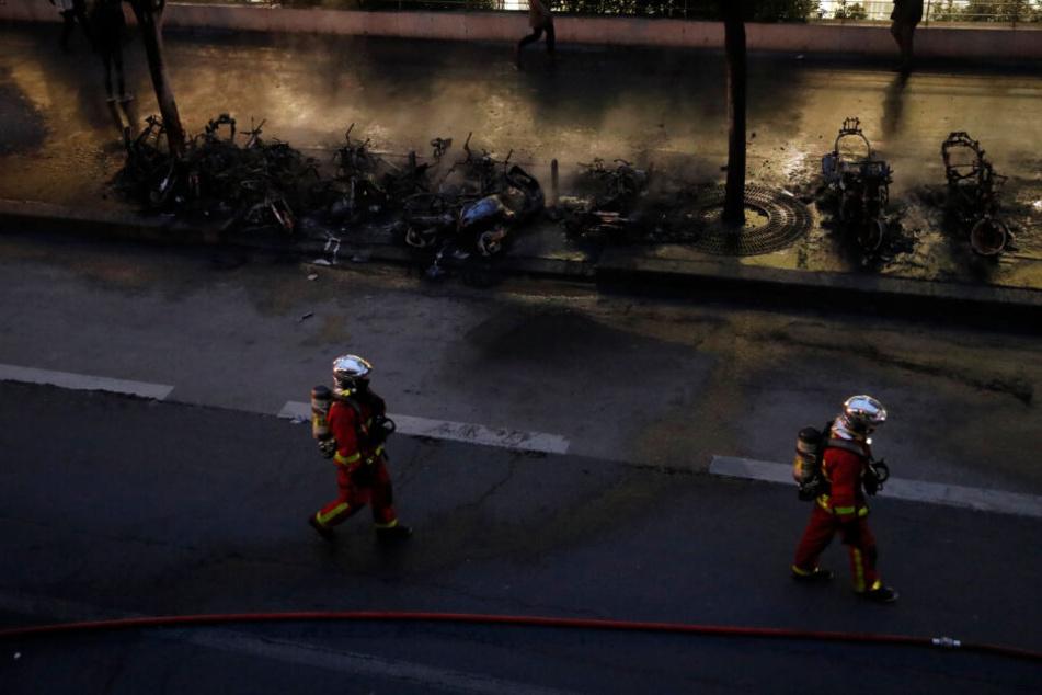 Einsatzkräfte der Feuerwehr gehen an verbrannten Motorrädern vorbei.
