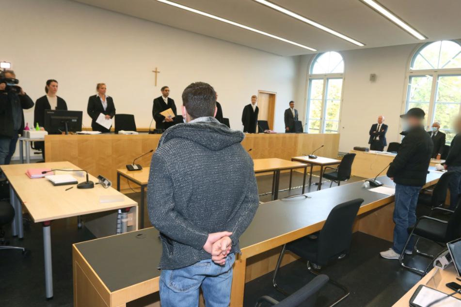 Der Hauptangeklagte (l) steht im Gerichtssaal des Landgerichtes neben den zwei Mitangeklagten. Drei junge Männer müssen sich vor Gericht verantworten weil sie an einer Auseinandersetzung mit tödlichem Ausgang in der Augsburger Innenstadt beteiligt waren.