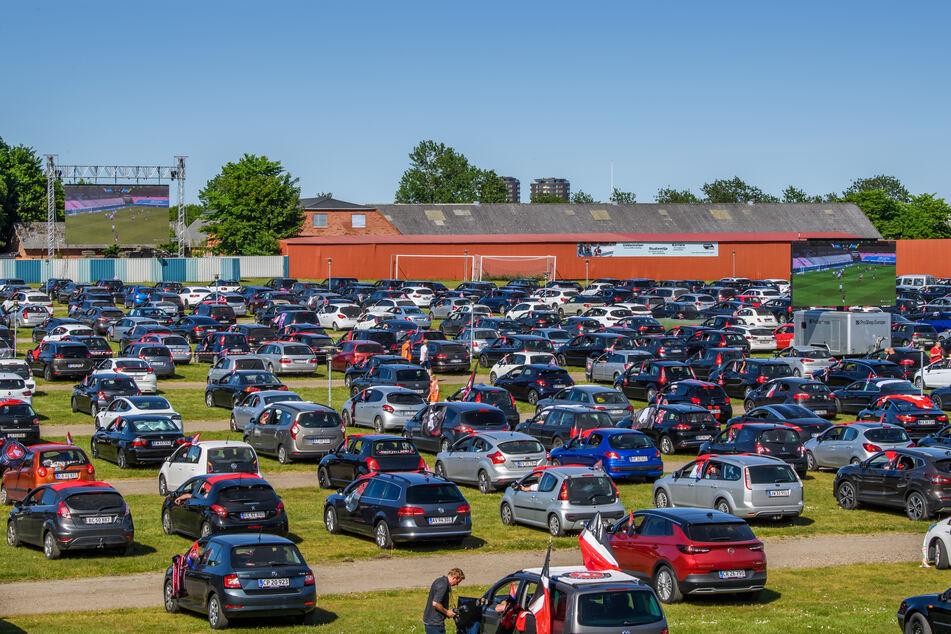 Fußballfans verfolgen auf dem Parkplatz der MCH-Arena das Spiel zwischen dem FC Midtjylland und dem AC Horsens, welches auf eine Leinwand übertragen wird.