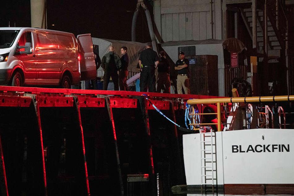 Lokale Strafverfolgungsbehörden sowie Such- und Rettungsteams helfen beim Entladen der Leichen derjenigen, die bei einem Brand eines Tauchbootes ums Leben kamen.