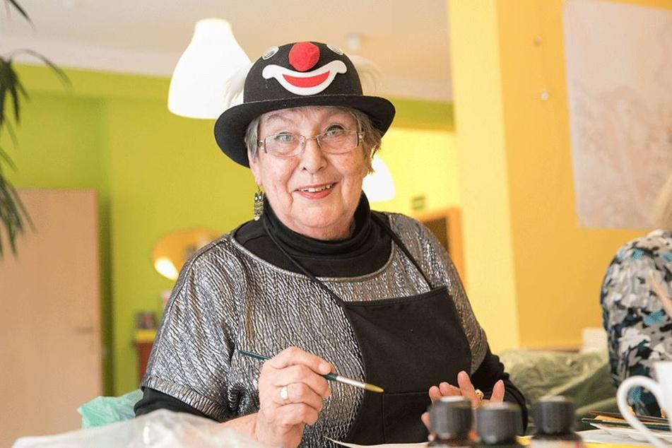 """Dass Karin Borkenhagen (74) mit Spaß und Freude zum Pinsel greift, zeigt schon ihr lustiger """"Arbeitshut""""... ."""