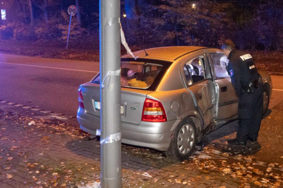 Ein Polizist untersucht das beschädigte Auto, dessen Fahrt am Laternenmast endete.