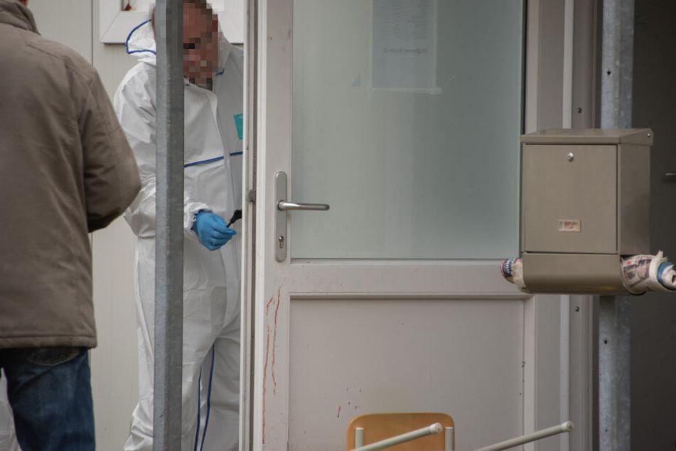 Ein Ermittler sichert Spuren an einer Tür.