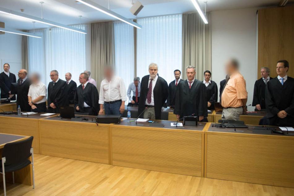 Die Angeklagten und ihre Verteidiger im Strafprozess um den Finanzdienstleister Infinus stehen im Gerichtssaal des Landgerichts Dresden.
