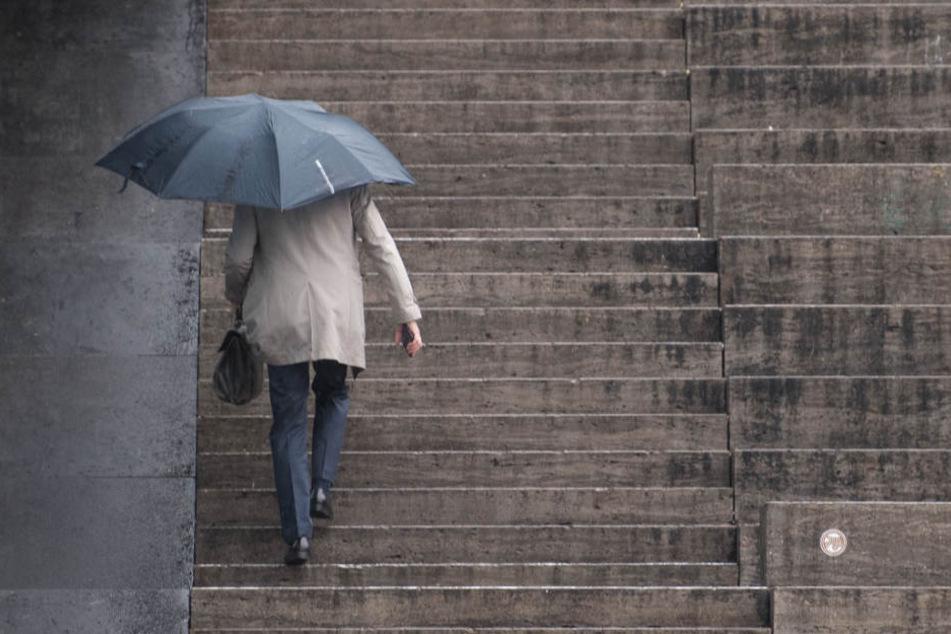 Ein Mann geht die Treppen auf dem Schlossplatz in Stuttgart bei Regen hoch. Regen sorgt für den Anstieg des Wasserstands im Rhein.