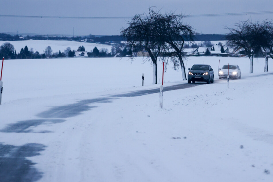 Stollberg: Autos fahren über eine verschneite Straße im Erzgebirge. Eine in der Nacht durchziehende Schneefront hat für reichlich neuen Schnee gesorgt.