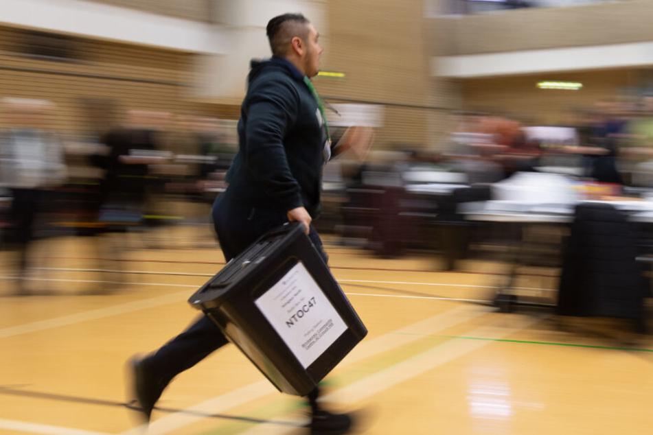 Mit einer Wahlurne in der Hand spurtet ein Wahlhelfer durch das Lokal.