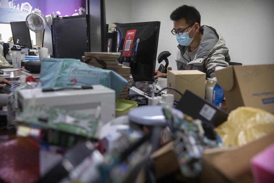 Ein Arbeiter trägt eine Gesichtsmaske bei der Arbeit in einem Technologieunternehmen in der Hauptstadt.