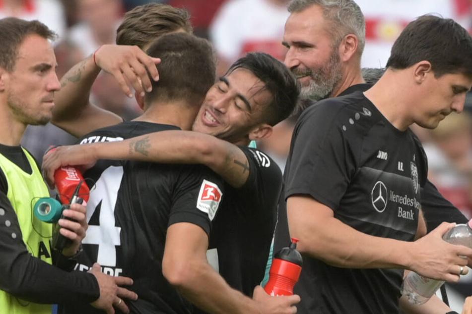 Nicolás González von Stuttgart (M) umarmt nach dem Sieg mit 2:3 gegen Regensburg seinen Teamkollegen Marc-Oliver Kempf. Dahinter beobachtet VfB-Coach Tim Walter das Geschehen mit voller Zufriedenheit.