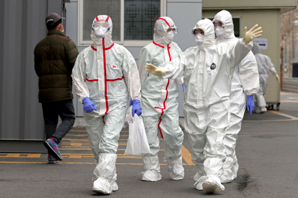 Medizinische Mitarbeiter in Schutzkleidung gehen über eine Straße, um zur Arbeit in ein Krankenhaus in Daegu (Südkorea) zu gelangen.