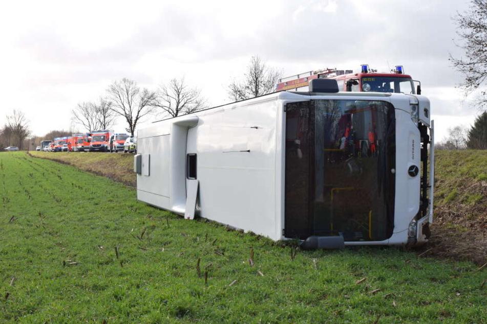 Der verunfallte Schulbus liegt umgekippt neben der Fahrbahn einer Landstraße.