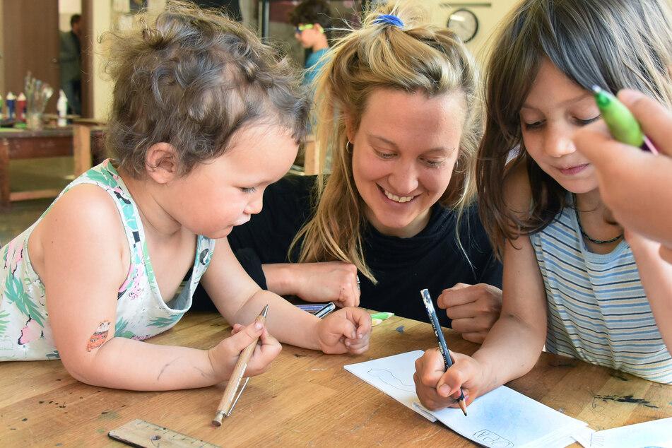 In der Schreib- und Druckwerkstatt im Buchkindergarten vom Verein Buchkinder e.V. malen und schreiben die Kinder Laszlo (l) und Rala (r) mit Werkpädagogin Janina Werner auf verschiedene Blätter, die anschließend zu einem kleinen Buch gebunden werden sollen.