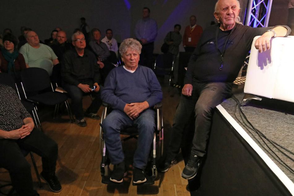 """Harry Jeske (82, l.) im Rollstuhl und Peter Meyer (80), beide Puhdys-Urgestein, sind 2019 vor der Bühne bei """"Stamping Feet feiert 50 Jahre Puhdys"""" in der Stadthalle."""
