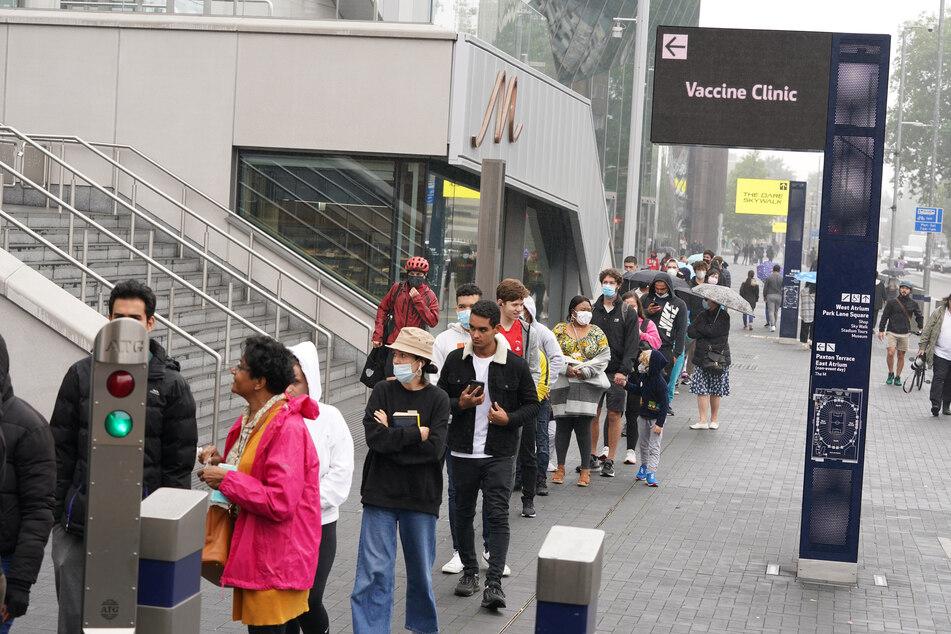 Menschen stehen Schlange vor einem Impfzentrum des National Health Service im Tottenham Hotspur Stadium.