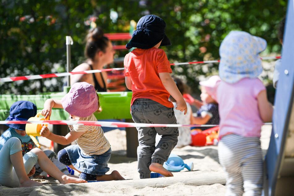 Kinder einer Krippen-Gruppe spielen auf dem Spielplatz der Kita. Absperrbänder regeln den Abstand.