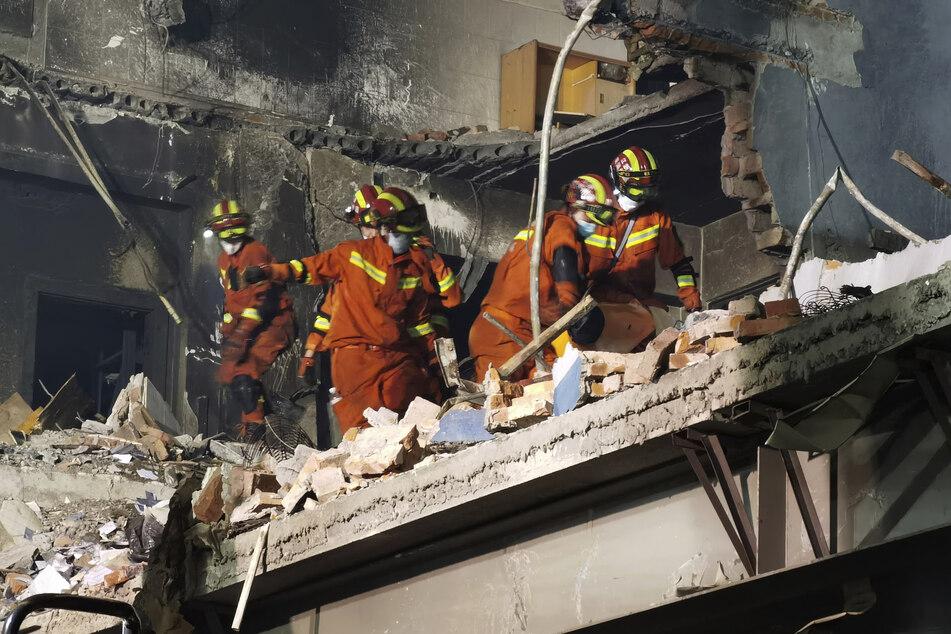Feuerwehrleute suchen nach Opfern in einem beschädigten Gebäude nach der Explosion des Tanklastwagens.