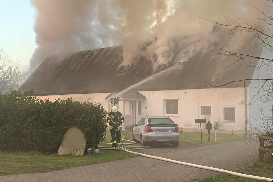 Dunkler Rauch steigt aus dem Dach des Wohnhauses.