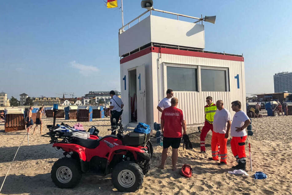 Einsatzkräfte beraten sich am Strand von Warnemünde.