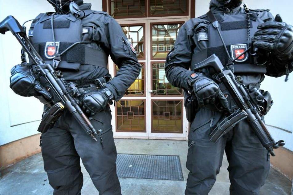Bewaffnete Polizeibeamte sichern einen Eingang zum Oberlandesgericht.