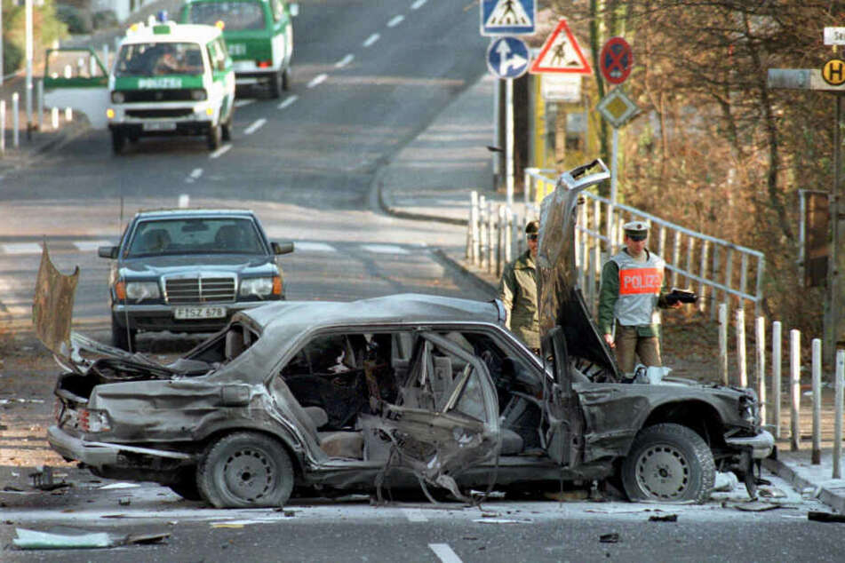 30. November 1989: Polizeibeamte in Bad Homburg neben dem Wrack der S-Klasse-Limousine von Alfred Herrhausen. Der Bankmanager starb bei dem RAF-Attentat.