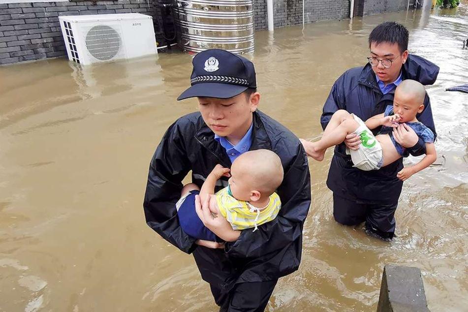 Polizisten helfen bei der Evakuierung von Babys und Kindern.