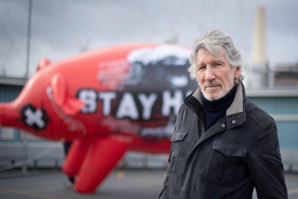 """Roger Waters (76) vor einem Ballon Schwein mit der Aufschrift """"Stay Human or Die"""" (Bleib menschlich oder stirb)."""