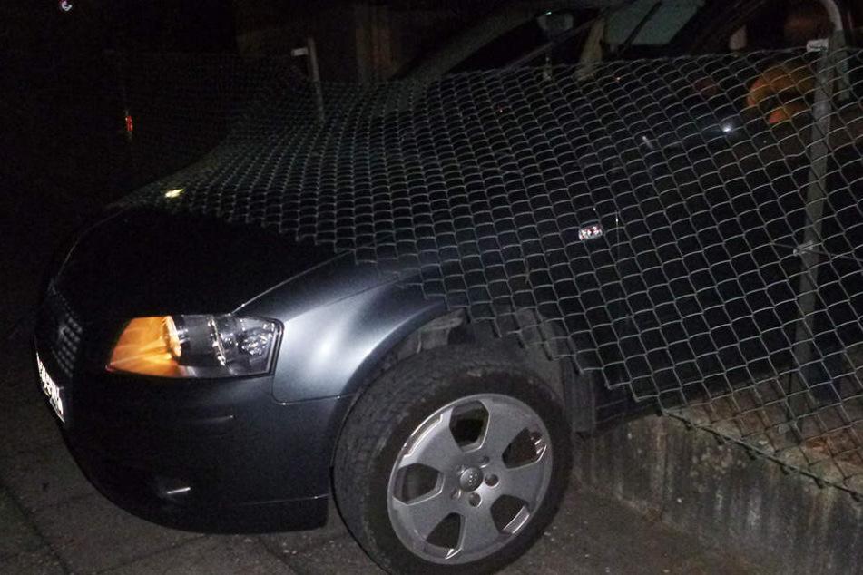 Der Audi steckte auf der Mauer im Maschendrahtzaun fest.