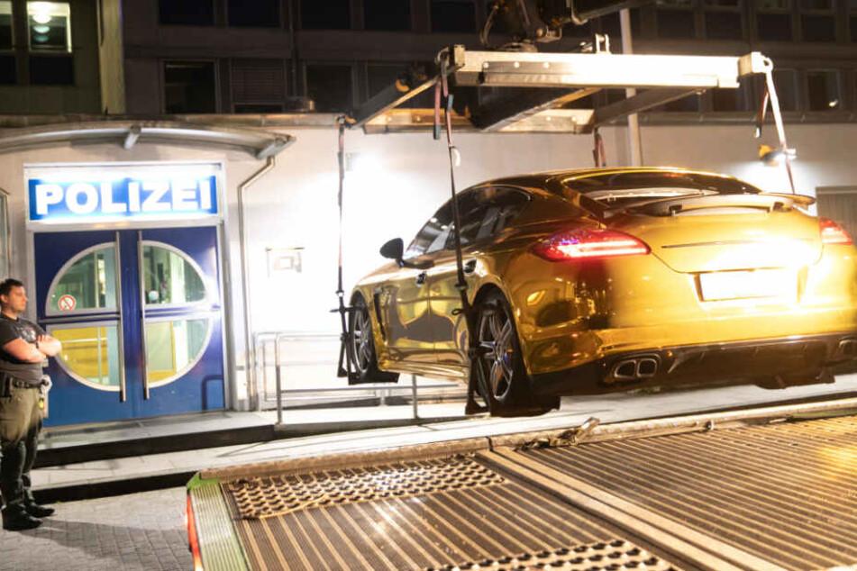 Die Polizei beschlagnahmt ein Fahrzeug, das mit Goldfolie überklebt ist.