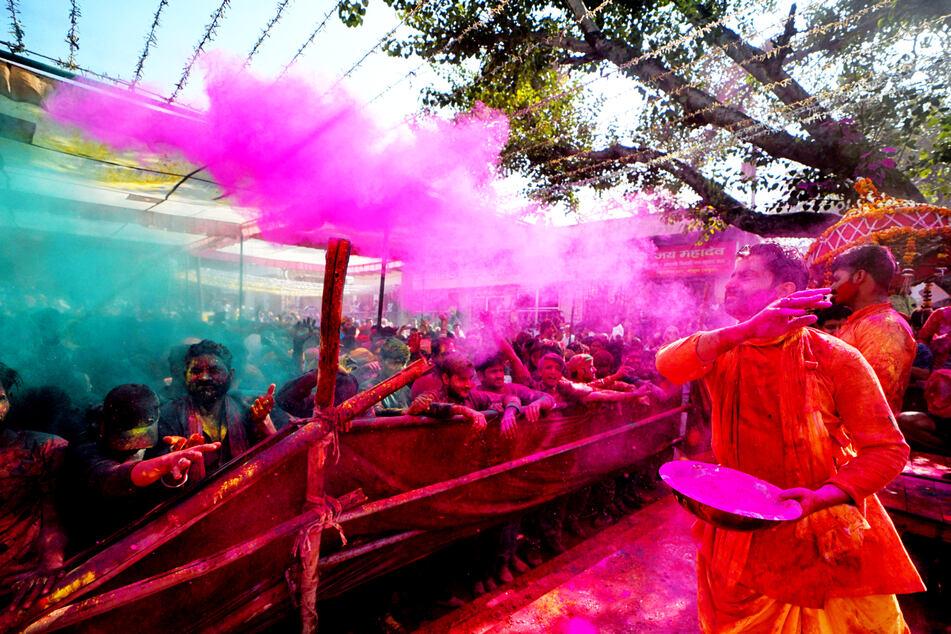 Hinduistische Anhänger zerstreuen während der Feierlichkeiten zum Holi-Fest farbiges Pulver und Wasser in Mathura, Indien.