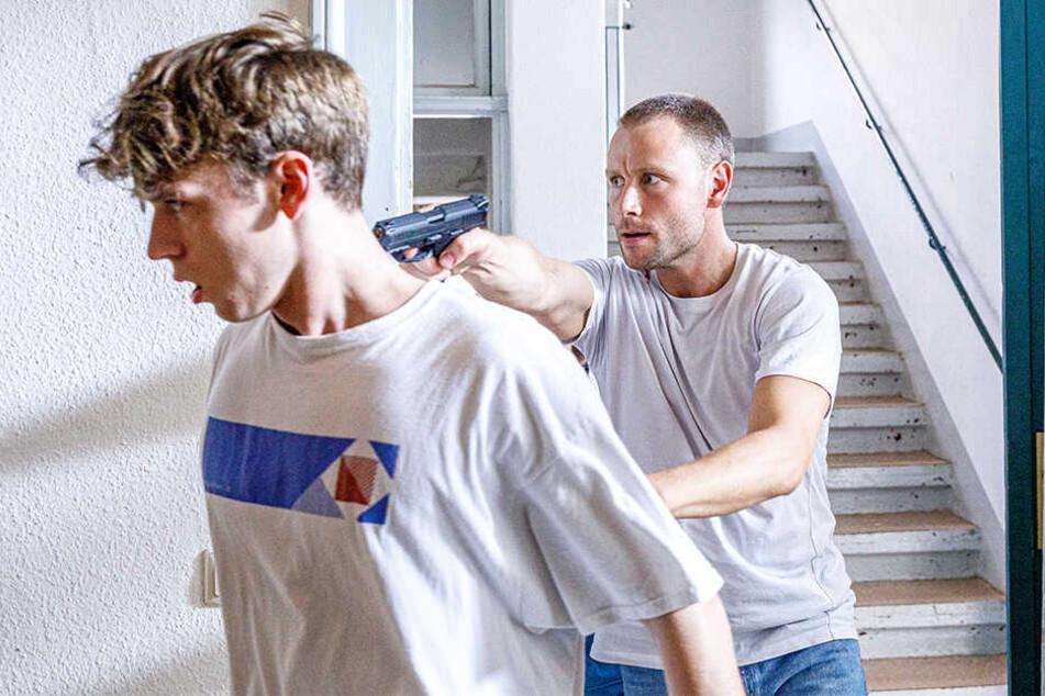 """Der bewaffnete Geiselnehmer Max Riemelt (35, """"Louis"""") drängt sein Opfer Emil Belton (20, """"Nico"""") durch den Flur."""