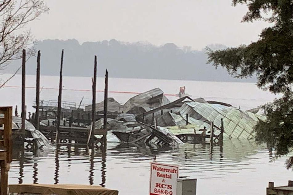 Ein Dock und viele Boote liegen nach einem Feuer zerstört im Wasser.