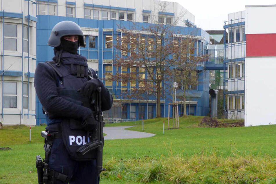 Ein Polizist steht am 24.11.2017 vor einem Gebäude der Universität Trier. Nach einer Amokdrohung ist am Freitag ein Tatverdächtiger festgenommen worden.