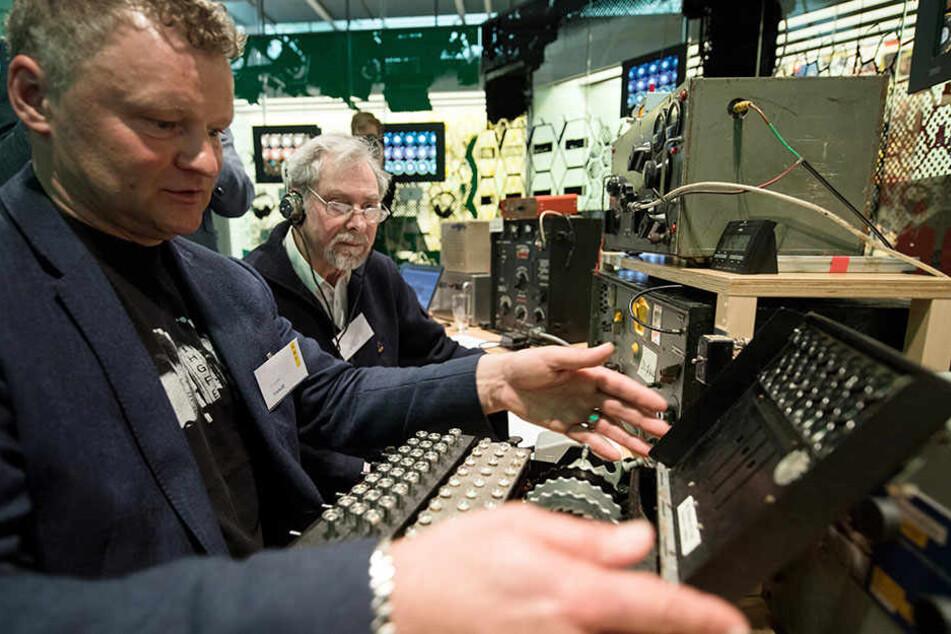 Geschäftsführer Jochen Viehoff (li.) sitzt an der Enigma Entschlüsselungsmaschine aus dem 2. Weltkrieg neben Amateurfunker Matthias Neuß.