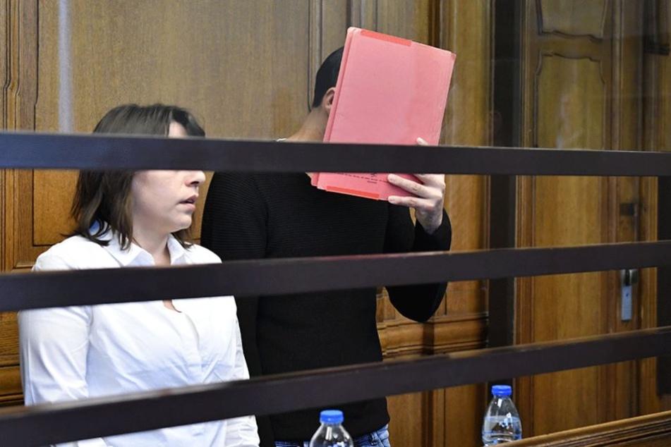 Der Angeklagte verbirgt am ersten Verhandlungstag sein Gesicht hinter einem Hefter.