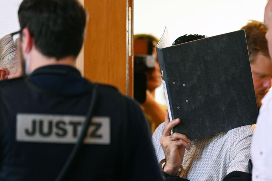 Einer von elf Angeklagten wird vor dem Prozessbeginn von einem Justizbeamten in einen Gerichtssaal im Landgericht gebracht. (Archivbild)