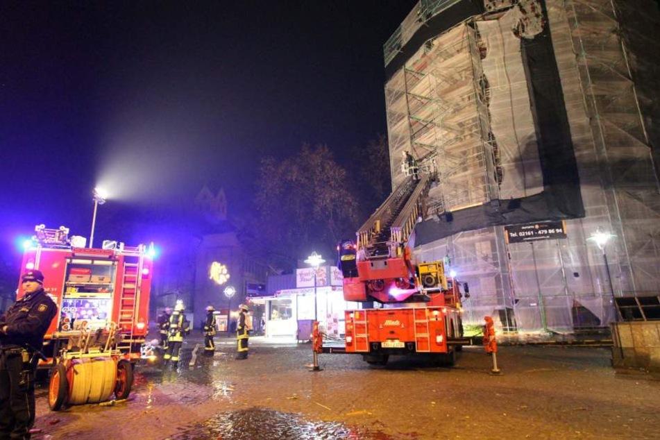 Einsatzkräfte arbeiten in der Silvesternacht an der Reinoldikirche in Dortmund: Eine Silvesterrakete hatte am Dach ein Fangnetz eines Baugerüsts in Brand gesetzt.
