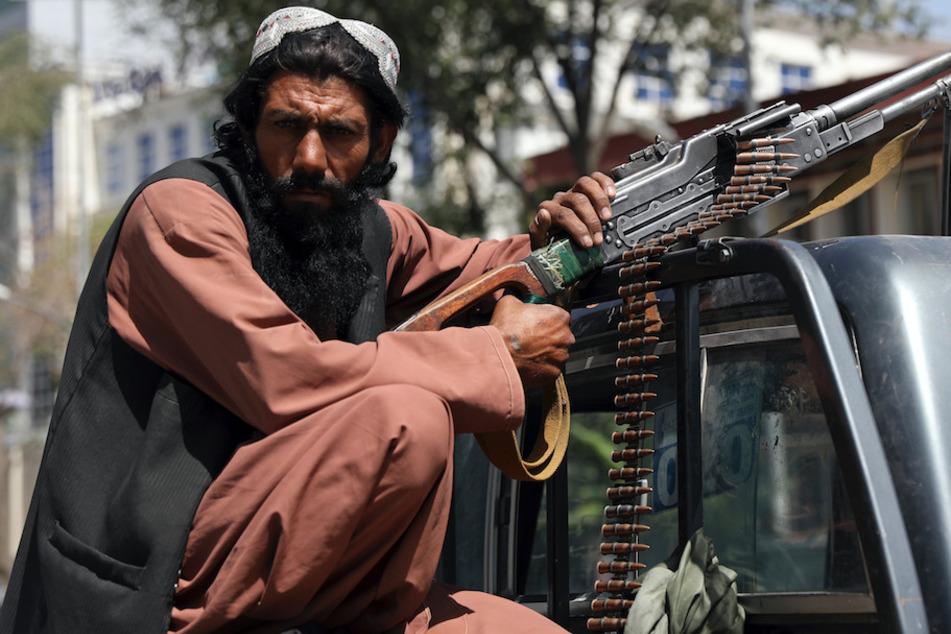 in Taliban-Kämpfer mit einem Maschinengewehr vor dem Haupttor zum Präsidentenpalast in Kabul.