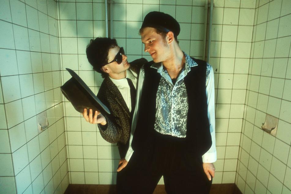 """Uwe Übelhauser (l.) und Peer """"DJ Emil"""" Ehmke posen als """"Disco-Team New Music"""" in einer VEB-Dusche, 1987."""
