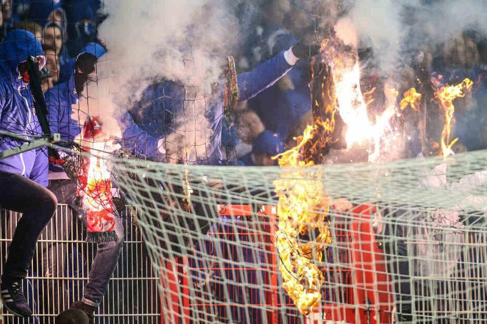 Maskierte Herthafans zünden Union T-Shirts an.