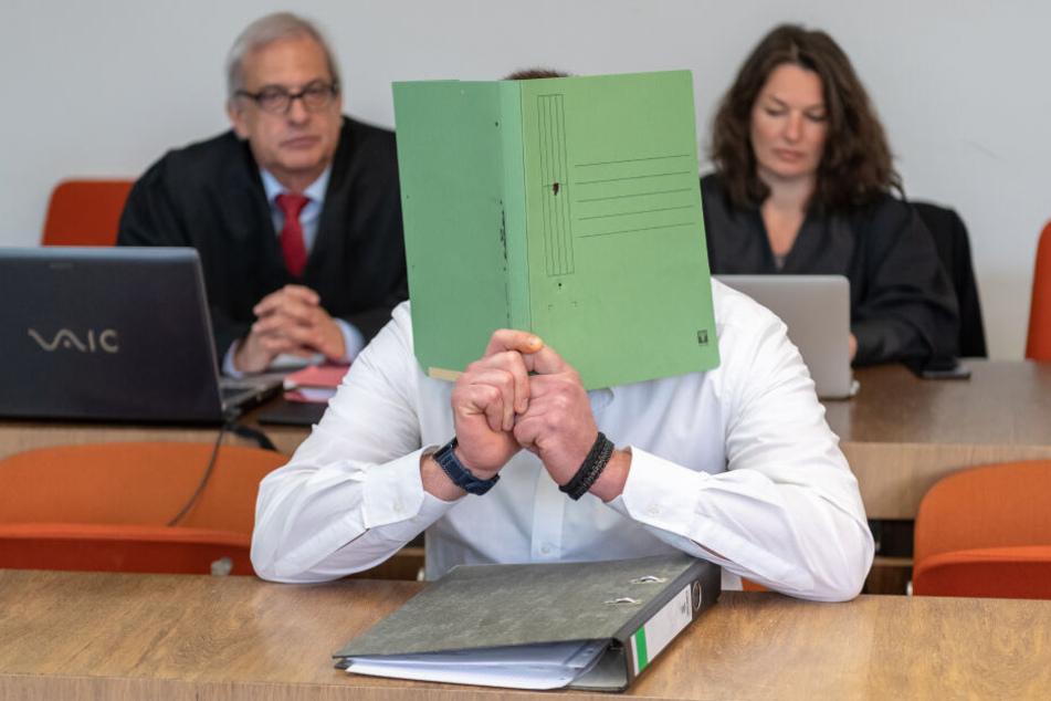 Der Angeklagte hält sich vor Prozessbeginn einen Aktendeckel vor das Gesicht.
