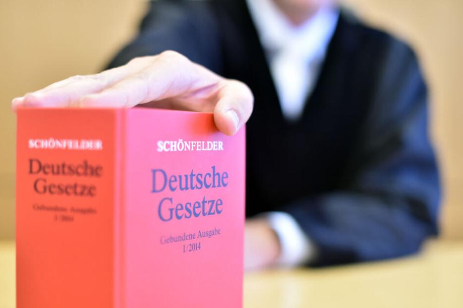 Ein Richter sitzt beim Oberlandesgericht auf der Richterbank und hält ein Buch mit den Deutschen Gesetzen.