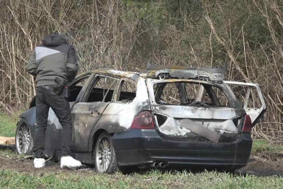 Ein Polizeibeamter neben dem ausgebrannten Fluchtauto in Köln. Beim Überfall in Limburg waren die Täter ähnlich vorgegangen (Archivbild).