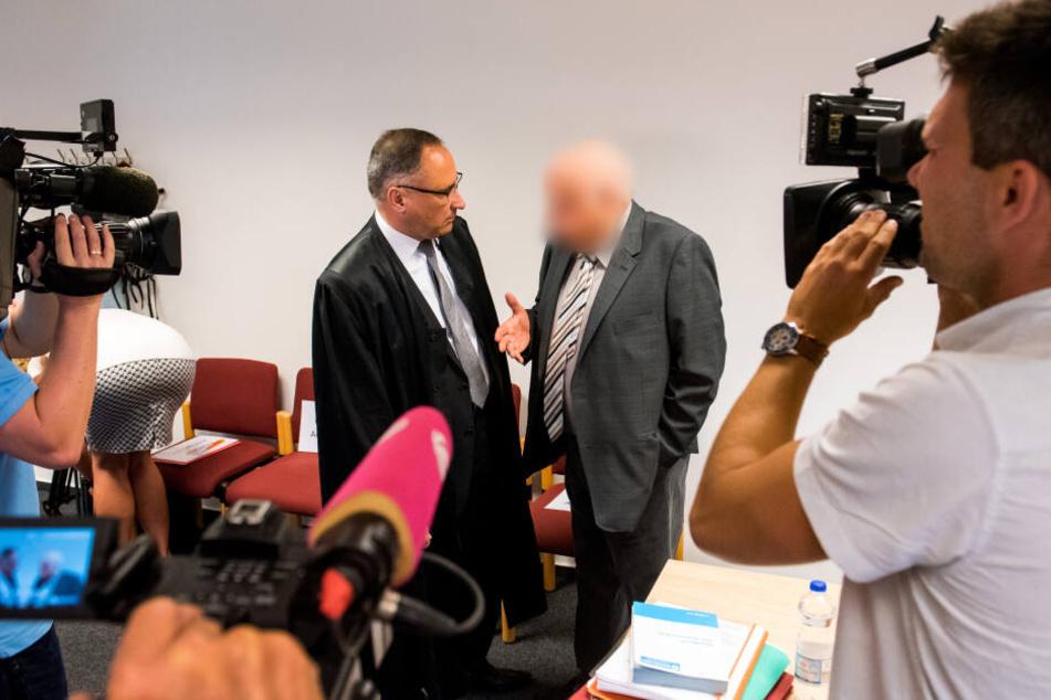 Detlef H. (rechts), Angeklagter und früherer Leiter der Lübecker Opferschutzorganisation Weißer Ring, spricht im Amtsgericht im Saal mit seinem Verteidiger.