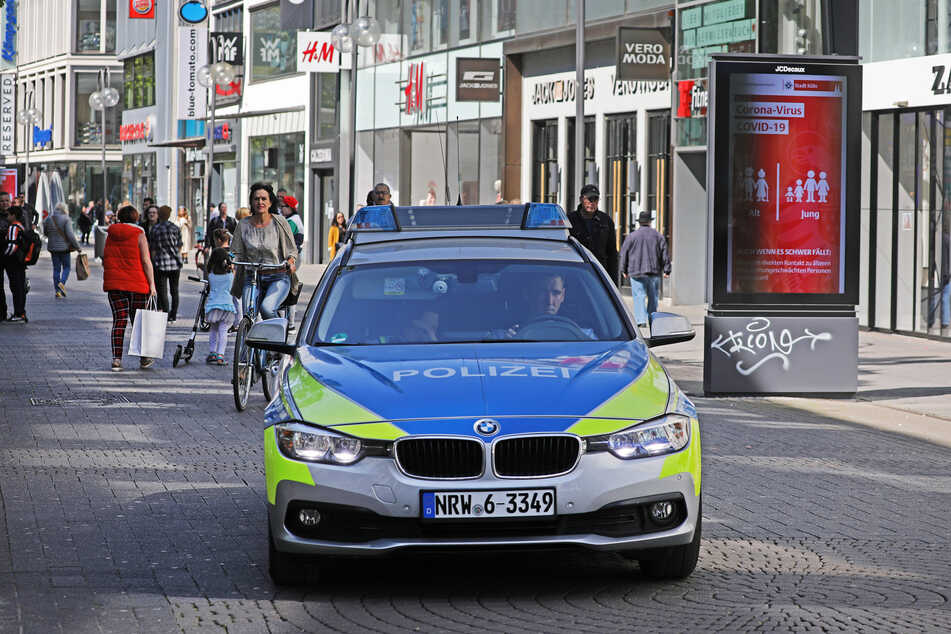 Eine Polizeistreife fährt durch eine Kölner Fußgängerzone.