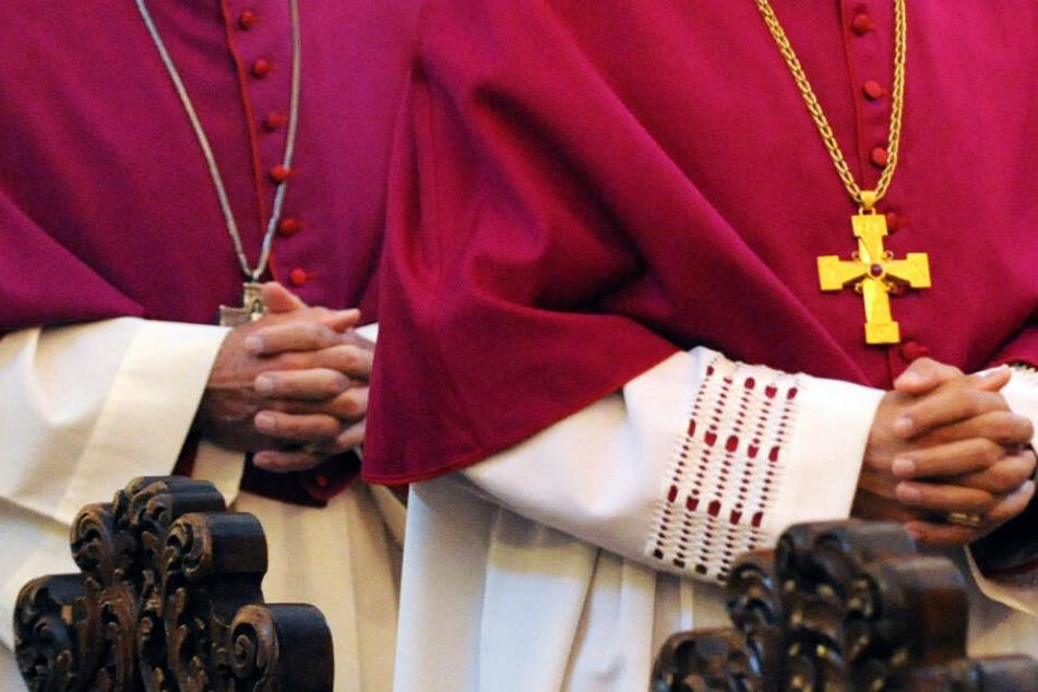 Zwei katholische Bischöfe haben die Hände zum Gebet gefaltet.