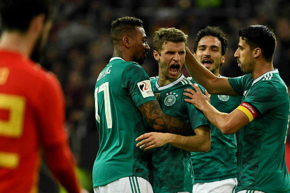 Von Jérome Boateng (l.) Mats Hummels (2. v.r.) und Sami Khedira (r.) wird Thomas Müller beglückwünscht.