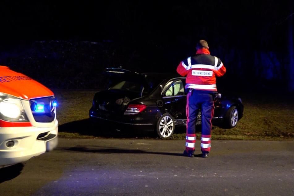 Ein Rettungssanitäter steht vor einem der Unfallautos.